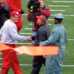 Coach Chryst and Coach Flood shake hands - goalpost flag still whipping in the wind
